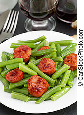 beans with chorizo on the plate and glass of red wine