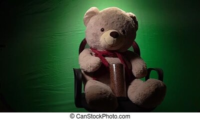 The bear in the hands of a buckwheat, covid19 green screen in the background, sits on a chair and spins