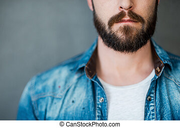 Beard is his style. Cropped image of young man wearing shirt while standing against grey background
