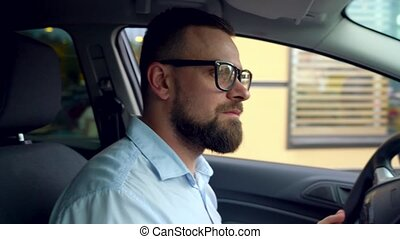 Beard man in a car after receiving his order at a fast food restaurant