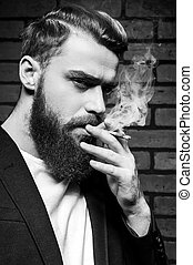 Beard man smoking. Black and white portrait of handsome young bearded man smoking a cigarette and looking at camera while standing against brick wall