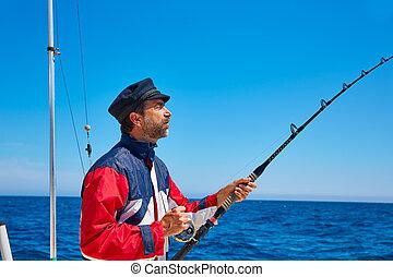 Beard sailor man fishing rod trolling in saltwater in a boat...