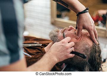Beard shaving in barber shop