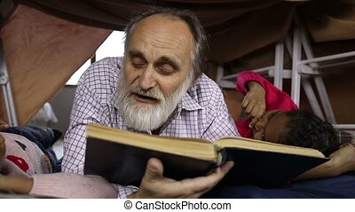 Bearded aged man and grandchildren reading a book - Bearded...