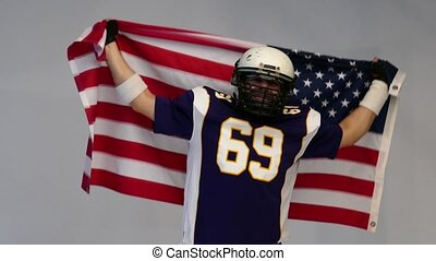 Bearded American football player in uniform, waving US flag.
