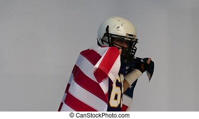 Bearded American football player in uniform, with US flag in his shoulders.