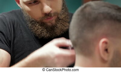 Bearded brutal man in a barber shop - Men's hairstyling and...