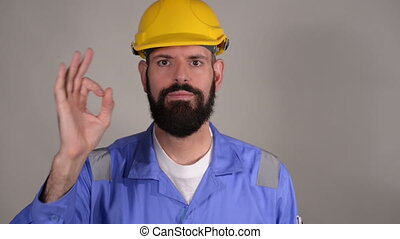 Bearded builder in hard hat showing ok gesture ,concept of success and approval over grey background