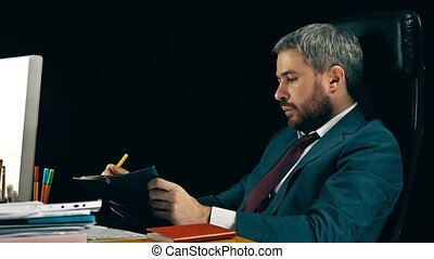 Bearded businessman checking the schedule in his personal organizer. Black background.