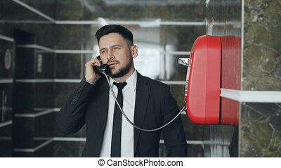 Bearded businessman dial red telephone talking with staff at...