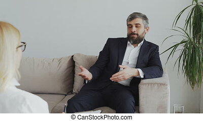 Bearded businessman explaining his problems to psychologist in office