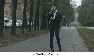 Bearded businessman in park alley talking by phone and writing in diary, working with notes at green park.