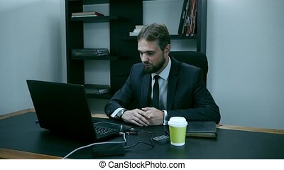 bearded businessman sitting in the office at the laptop,...