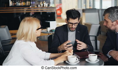 Bearded businessman speaking with male and female partners...