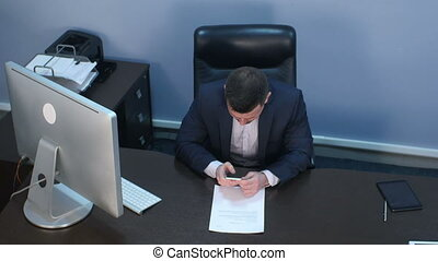 Bearded businessman using smartphone sitting at desk in office