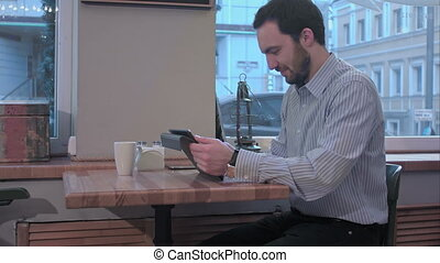 Bearded businessman using tablet computer in coffee shop in...