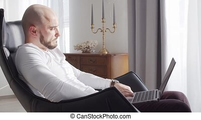 Bearded businessman working at home sitting in armchair and ...