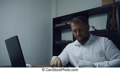 bearded businessman working in the office on a computer, male looking at his work plan, slow motion
