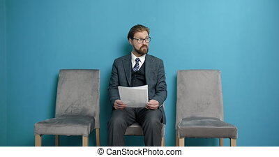 Bearded male candidate in formal clothing and eyeglasses holding his resume while sitting on grey chair at waiting room. Mature employee become angry about interview result.