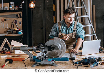 Bearded carpenter planning woodworking project