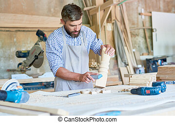 Bearded Carpenter Sanding Stair Posts in Shop - Portrait of...