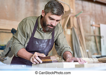Bearded Carpenter Sanding Wood in Shop - Portrait of mature...