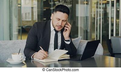 Bearded Caucasian businessman using laptopc omputer, talking...