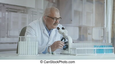 Bearded Caucasian male researcher wearing protective glasses and working with a microscope spbas. scientist using microscope in a laboratory. Search for coronavirus vaccine. High quality 4k footage