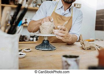 Bearded ceramist having creative ideas while using ceramics...