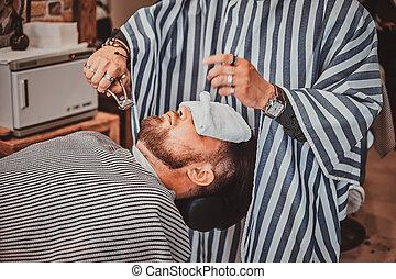 Bearded client just got good beardcare from trendy barber.