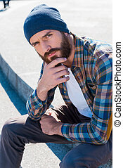 Bearded confidence. Handsome young bearded man holding a hand on a chin while sitting outdoors