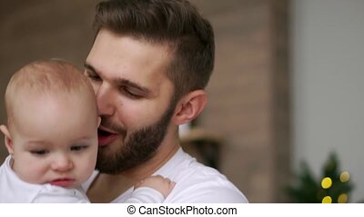 Bearded dad kissing baby. Close up of happy father with...