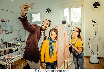 Bearded father making selfie with his cute loving children