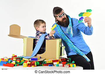 Bearded father play with little son. Toys, interesting games with child. Loving dad bought new developing toys for his son. Little pilot in his carton airplane. Travel, airport and adventure. Friends