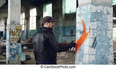 Bearded graffiti artist is painting on pillar in old abandoned building using aerosol paint. Modern youth subculture, creative people and street art concept.