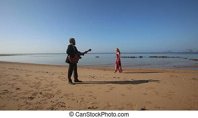 bearded guitarist in black plays on beach by girl in red
