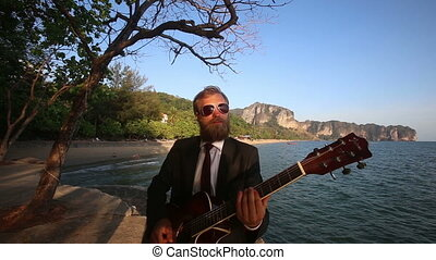 bearded guitarist in black suit plays gitar against served...