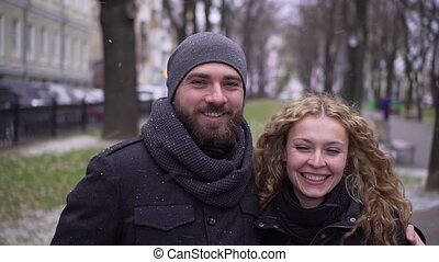 Bearded guy and curly girl look at the camera and smile in...