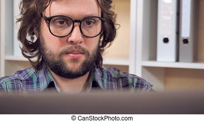bearded guy close a laptop posing with smile
