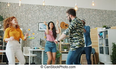 Bearded guy dancing in office while coworkers clapping hands having fun together