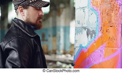 Bearded guy in casual clothing is drawing abstract image...