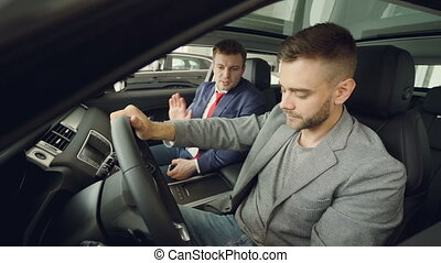 Bearded guy is discussing car features with salesman sitting...