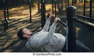 Bearded guy is exercising outdoors doing pull-ups on low...