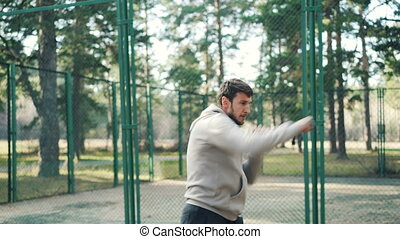 Bearded guy is training in park making boxing movements...