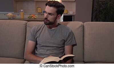 Bearded guy sits on sofa and reads thick book. He turns on...