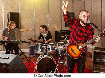 Bearded guy soloist playing guitar in studio
