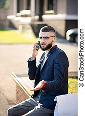 Bearded handsome businessman speaking with colleague by phone