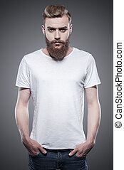 Bearded handsome. Handsome young bearded man holding hands in pockets and looking at camera while standing against grey background