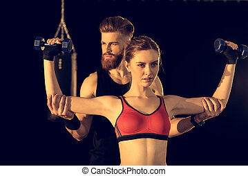 Bearded handsome man training young sporty woman with dumbbells