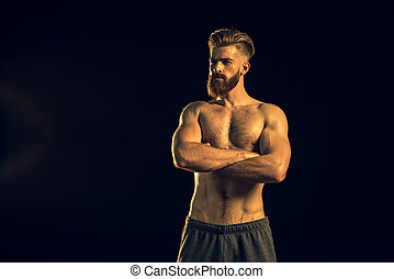 bearded handsome man with crossed arms standing on black